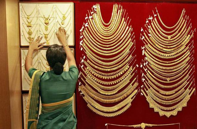 5881b046e4d0 A saleswoman arranges a gold necklace inside a jewellery showroom in Kochi