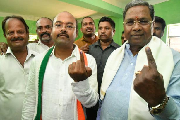 Karnataka Chief Minister Siddaramaiah and his son Yathindra after cast their votes at the Suddaramana Hundi polling centre in Mysuru on May 12, 2018.
