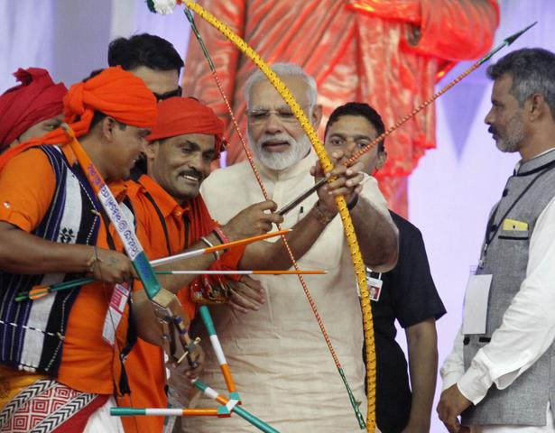 Narendra Modi Is Being Presented A Bow And Arrow By Group Of Tribals During Public Meeting In Dabhoi After Inauguration The Sardar Sarovar Dam