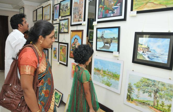 Visitors looking at the paintings at an art exhibition in tiruchi on friday photo