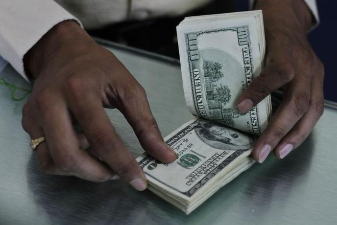 An Indian Man Counts U S Dollars At A Western Union Money Transfer Center In Ahmadabad