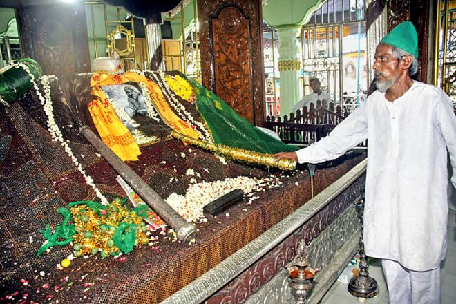Fakir cleans the holy tomb of Hazrath Kale Mastan Shavilla at the Mastan Dargah in Guntur on Monday. Photo: T. Vijaya Kumar