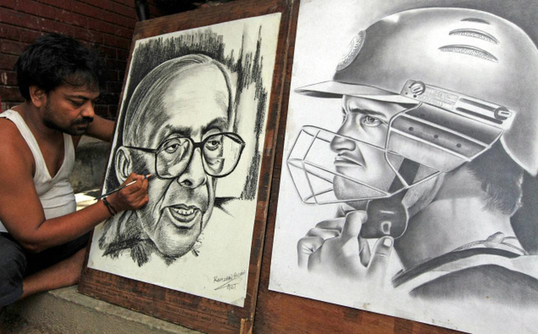 A pavement artist gives final touches to a pencil sketch of late cpim leader jyoti basu beside another sketch of cricketer sourav ganguly in kolkata on