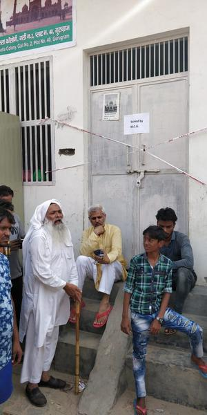 Members of the Muslim community sit outside the sealed mosque as a mark of protest at Sheetla Mata Colony in Gurugram on Wednesday.
