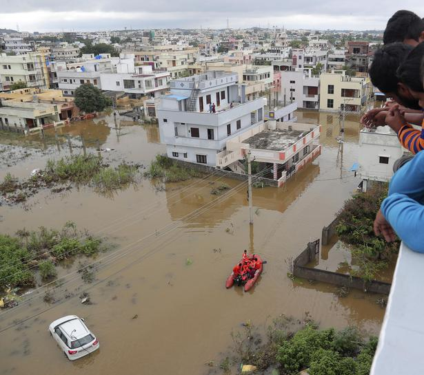 Residents look at an inundated street after heavy rains in Hyderabad on October 14, 2020.