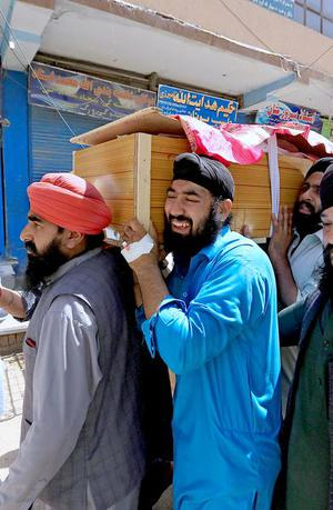 Afghan Sikh men carry the coffin of one of the victims of the July 1 blast in Jalalabad.