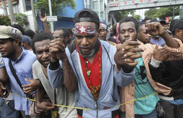 "A Papuan activist with his forehead painted with banned separatist flag the ""Morning Star"" marches with others during a rally in Surabaya, East Java, Indonesia, Saturday, Dec. 1, 2018."