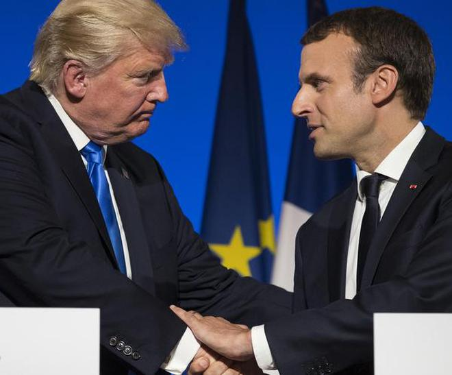 In this July 13, 2017 file photo, U.S. President Donald Trump and French President Emmanuel Macron shake hands at the conclusion of a news conference at the Elysee Palace in Paris.