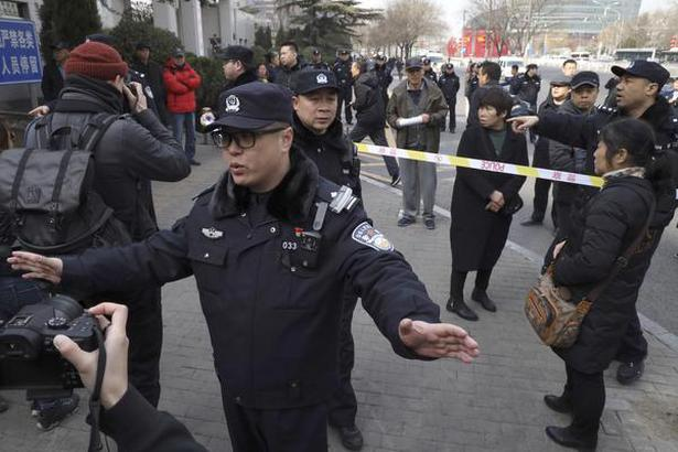 Chinese police officers push back journalists from relatives of passengers on board the missing Malaysia Airlines Flight 370 who have gathered outside the Chinese Foreign Ministry demanding answers, in Beijing, on Friday.