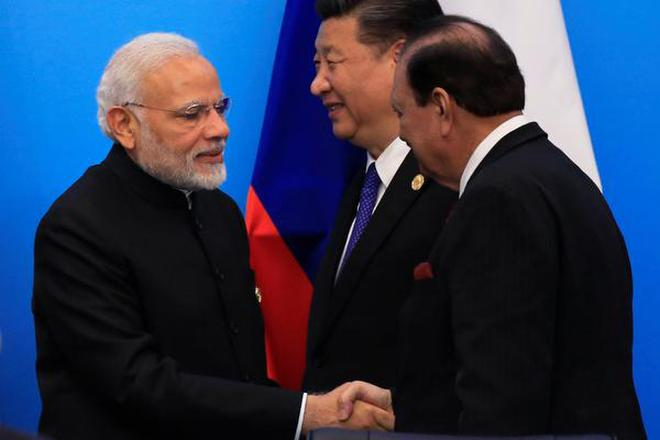 Pakistan's President Mamnoon Hussain shakes hands with India's Prime Minister Narendra Modi as China's President Xi Jinping walks behind them at a signing ceremony during Shanghai Cooperation Organization (SCO) summit in Qingdao, Shandong Province, China on Sunday.