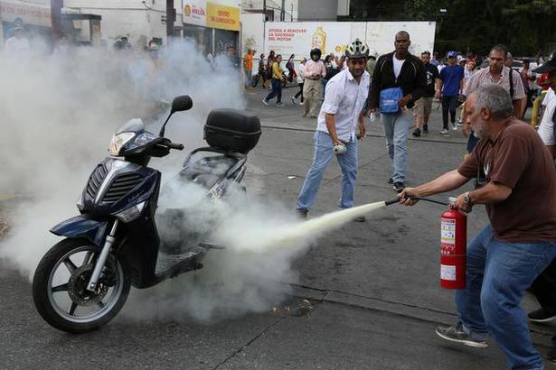 A man tries to extinguish a motorcycle on fire during a protest against the government of Nicolas Maduro on March 9, 2019 in Caracas, Venezuela.