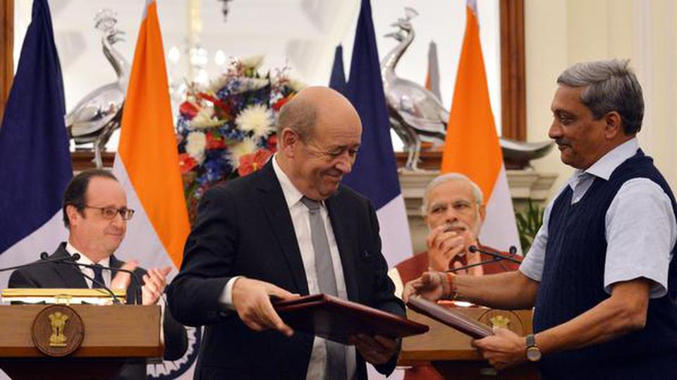 Defence Minister Manohar Parrikar exchanges documents with his French counterpart Jean-Yves Le Drian after signing an MoU on the purchase of 36 Rafale fighter aircraft in the presence of French President Francois Hollande and Prime Minister Narendra Modi at Hyderabad House in New Delhi on January 25, 2016.