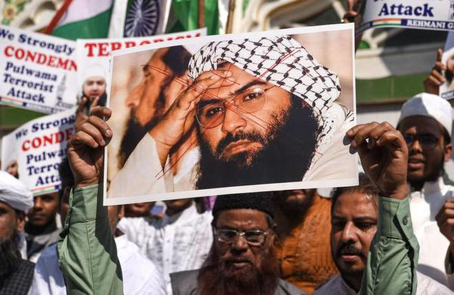 Indians hold a scratched photo of Jaish-e-Mohammad group chief, Maulana Masood Azhar, as they shout slogans against Pakistan during a protest in Mumbai on February 15, 2019, the day after the Pulwama attack.
