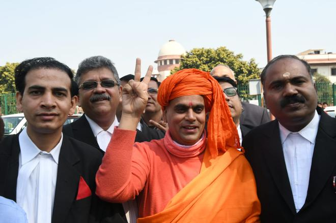 Swami Chakrapani, president, Akhil Bharat Hindu Mahasabha, flashes victory sign after Supreme Court sent the Ayodhya title dispute for mediation.