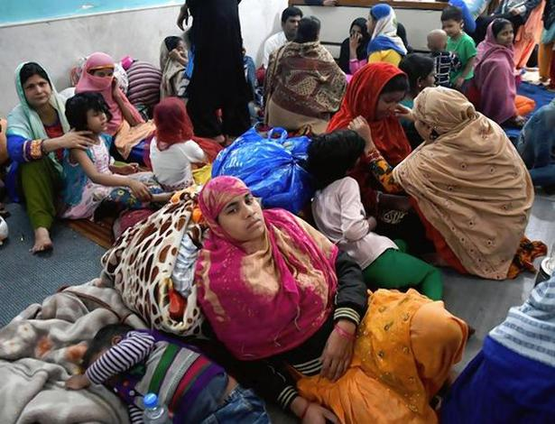 Belongings gone: Families affected by the violence in northeast Delhi taking shelter in a private relief camp in Chaman Park on Saturday, while (right) residents of Shiv Vihar inspecting the damage to cars in a parking lot.