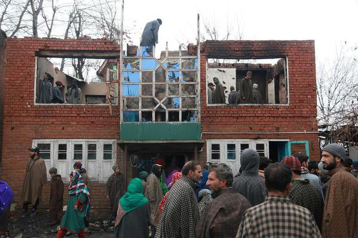 Onlookers outside a house that was damaged in a gun battle between suspected militants and security forces in Jammu and Kashmir's Pulwama district on February 1, 2019.