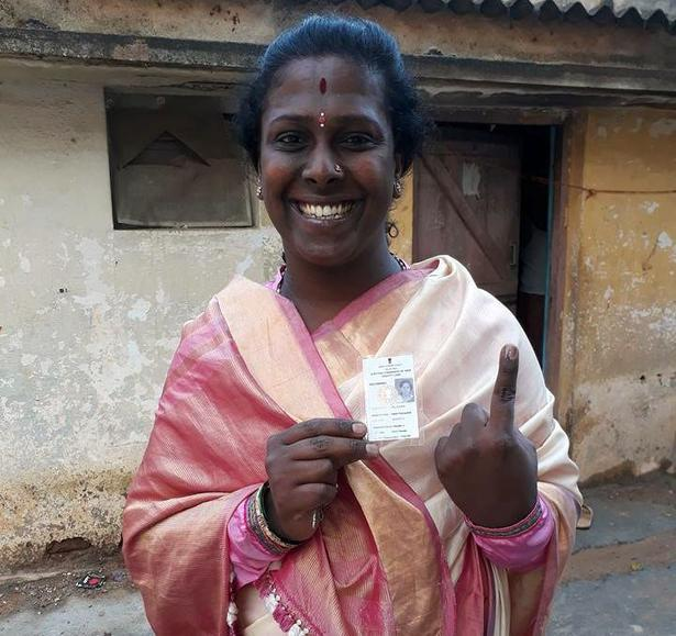 Akkai Padmashali shows her ink-marked finger and voter ID card after casting her vote.