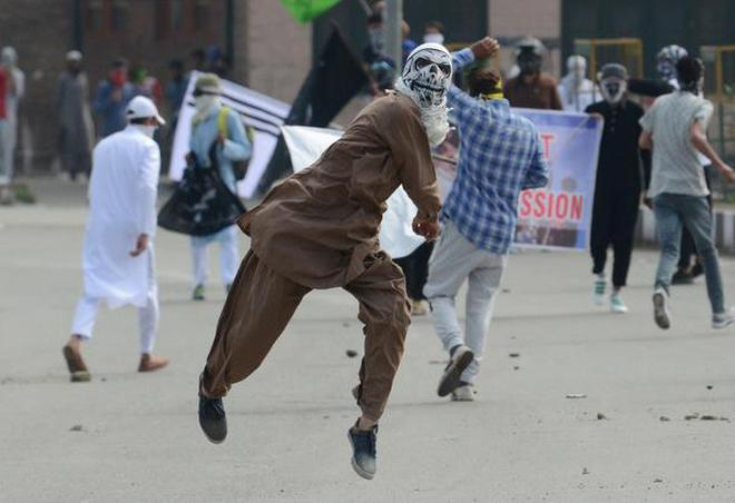 Protesters throw stones during clashes with security forces in Srinagar on Saturday.