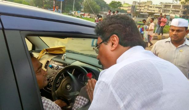 A Congress member pleads a motorist to take part in the bandh by offering roses in Bhubaneswar on Monday.
