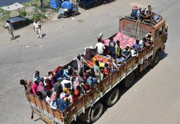 Migrant workers travelling in a truck in Patna, to get to their hometowns. Photograph used for representational purposes only
