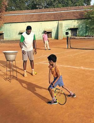J. John Selvakumar Pandian teaching tennis techniques to a beginner in Tiruchi.
