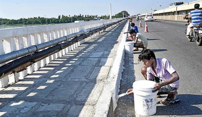 With new slabs:Workers engaged in painting the footpath laid on the old Cauvery bridge in Tiruchi on Friday.M. SrinathM_SRINATH