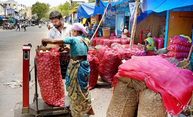 A wholesale trader weighs and sorting the onions at Gandhi Market in Tiruchi on Saturday.M. MoorthyM_Moorthy